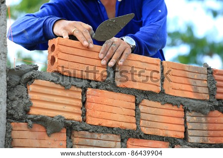 worker working on wet layer concrete, brick wall