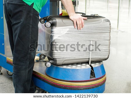 Worker wraps suitcase with a transparent film before travel by airplane for security reason and safety protection from damage. Additional packing of baggage at the airport terminal