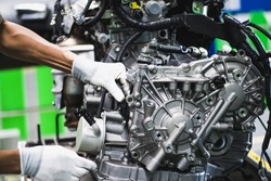 Workers are assembling engines in factories, which are at the heart of the car. (Automotive industry)