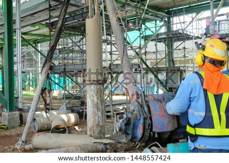 Workers are controlling the tripod rig machine is drilling holes in the construction site for concrete piles work and reinforced elements cast into drilled holes to be the foundation.
