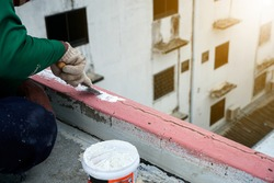 Workers are fixing cracks in the floor, spreading plaster using trowel, Repairing waterproofing deck flooring.