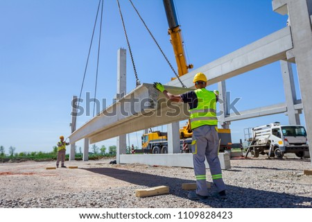Workers are helping mobile crane to manage concrete joist for assembly huge construction.