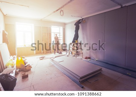 Workers are installing plasterboard (drywall) for gypsum walls in apartment is under construction, remodeling, renovation, extension, restoration and reconstruction. #1091388662