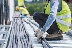 Workers are moving cables in construction sites.