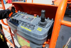 Workers are use control panel to driving the Orange articulate boom lift or telescopic boom lifts and bucket crane mounted on truck to safety for working at heights and articulating boom lift.