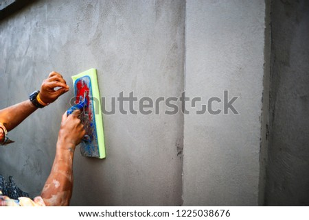 Workers are using a trowel plaster outside walls.