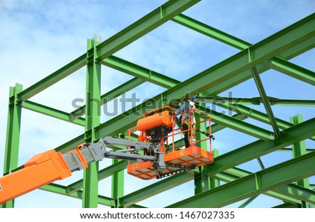 Workers are working on the Orange articulate boom lift or telescopic boom lifts and bucket crane mounted on truck to safety for working at heights and articulating boom lift reaching high up.