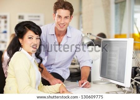 Workers At Desk In Busy Creative Office