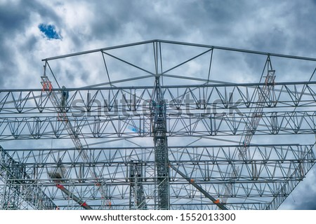 Workers build large metal structures for the concert stage. Cloudy sky with thunderclouds