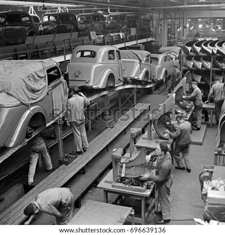 Workers building cars in factory