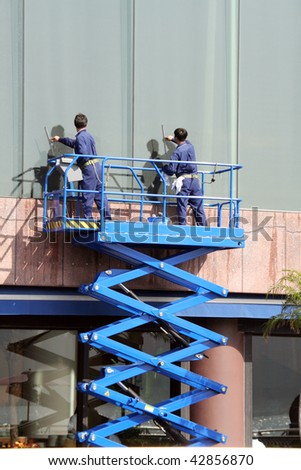 Workers cleaning glass