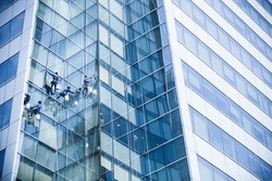 Workers cleaning windows of a tall building