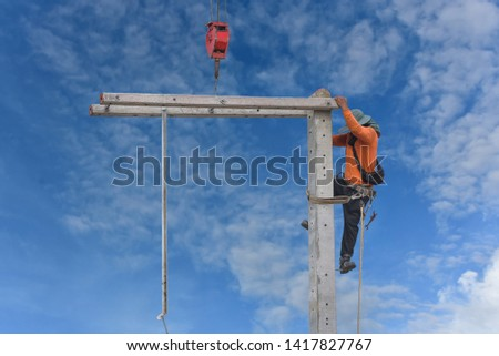 Workers climbing electric poles with crane lifting equipment and wearing equipment protective safety harness on blue sky.
