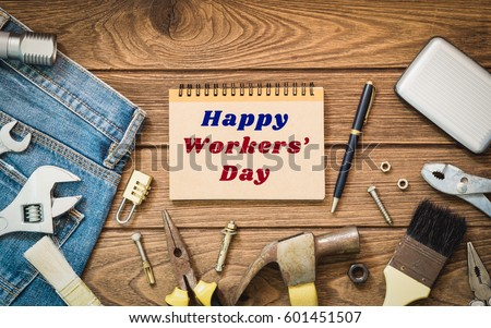 Workers\' day background concept - Jeans, many handy tools, notebook with happy workers\' day text , wooden background top view