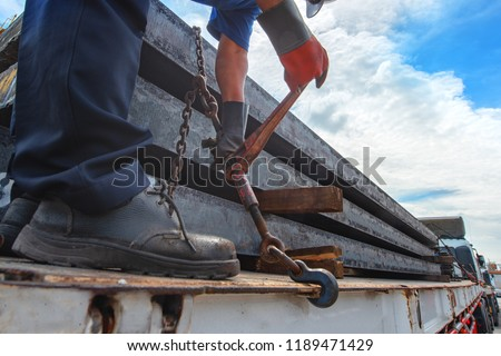 workers driver of the trailer lorry is lashing securing steel slab on the trailer, lashing securing goods by tightening chain for lashing before delivery