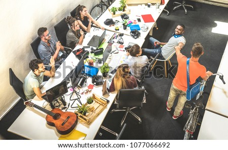 Workers employee group having fun at urban alternative studio with young entrepreneur coming in with vintage bike - Business concept of human resource on working time - Start up internship at office