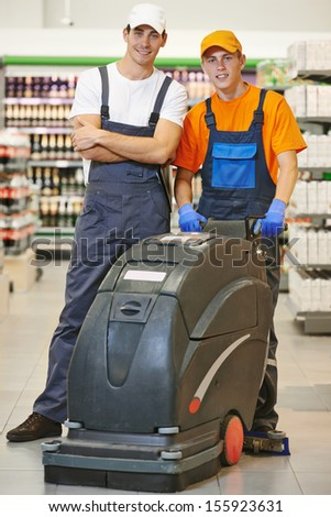 Workers. Floor care and cleaning services with washing machine in supermarket shop store