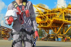 Workers hand holding safety helmet with wearing safety harness in Construction site. Fall arrestor device for worker safety body harness safety concept.