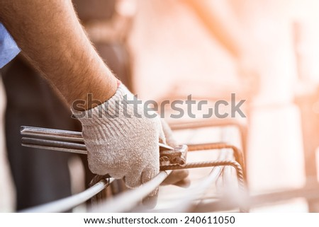workers hands using steel wire and pincers to secure rebar before concrete is poured over it. Selective focus on center portion of image. Construction site worker , closeup hands , form work