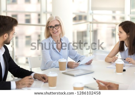 Workers headed by team leader mature female gathered together in conference room discussing business matters new project review report sales statistics sitting at desk in light modern conference room