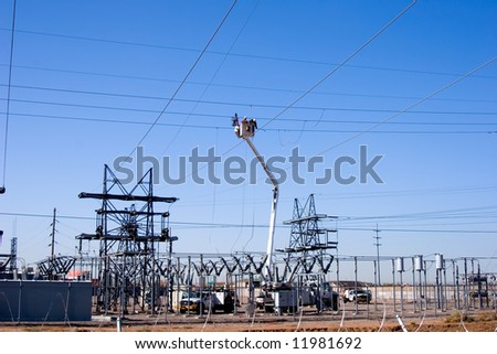 Workers in a bucket working on high tension power wires.