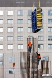 Workers in bright orange vests  are using a crane at a height to mount the formwork on a metal frame made of steel reinforcement against the background of the window facade of the new house. Vertical