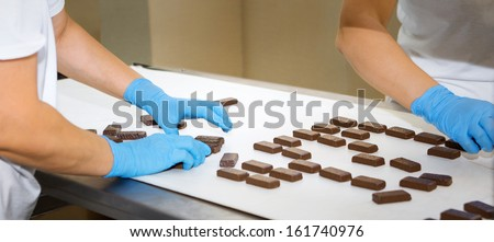 Workers in gloves working on automated production lines in the factory cakes