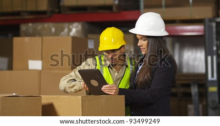 Workers in warehouse use digital tablet