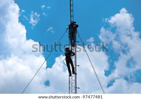 Workers install cellular antenna