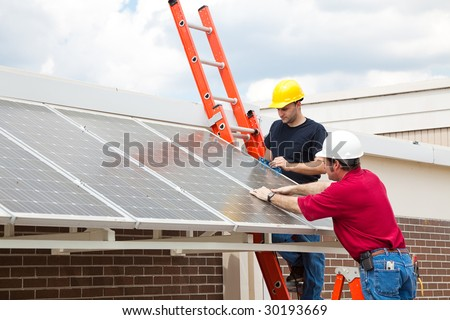 Workers install energy efficient solar panels on the roof of a building.