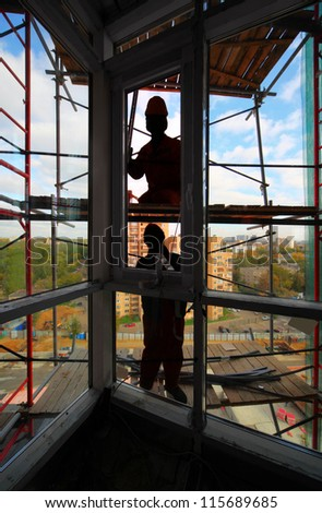 Workers install plastic windows in new building