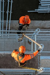 Workers installing scaffolding from above