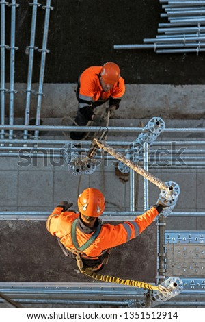 Workers installing scaffolding from above #1351512914