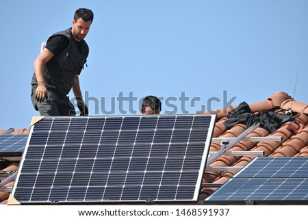 Workers installing solar panels on residential house roof