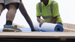 Workers lay an insulating layer of non-woven fabric on the roof.