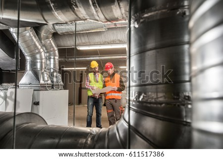 Workers making final touches to HVAC system. HVAC system stands for heating, ventilation and air conditioning technology. Team work, HVAC, indoor environmental comfort concept photo.