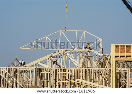 Workers move a roof truss into position on a new house under construction in a suburban neighborhood.