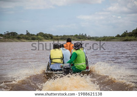 workers on a boat navigating the Doce river, in an area flooded by rain Foto stock ©