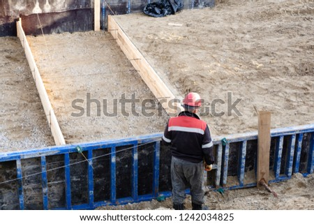 workers on a construction site to make the cement Foundation for the housing Foundation building site fabrication of reinforcement metal framework for concrete
