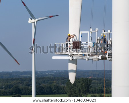 Workers on a hanging platform repair a damaged rotor blade on a wind turbine Foto d'archivio ©