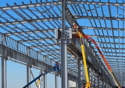 Workers on aerial work platforms build the metal structure of the roof of a large building.