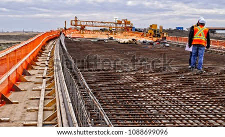 Workers on bridge deck panels with reinforcing steel bars on top of concrete girders prior to pouring concrete over reinforcing steel to provide strength and integrity to the bridge to support traffic #1088699096