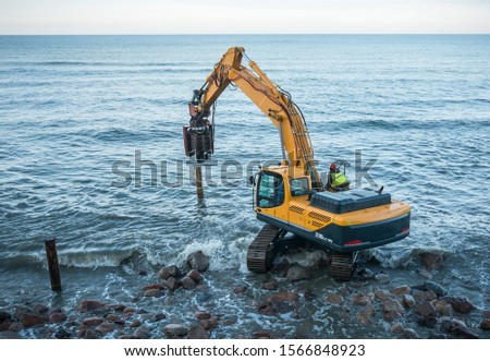 Workers on the sea beach. Sea beach fortification. Pile-driver.