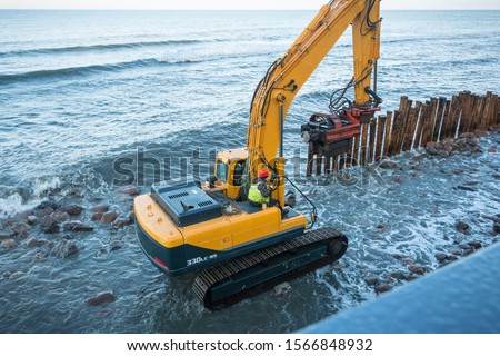 Workers on the sea beach. Sea beach fortification. Pile-driver. #1566848932
