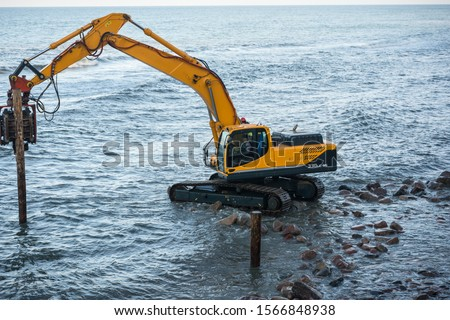 Workers on the sea beach. Sea beach fortification. Pile-driver. #1566848938