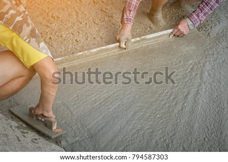 Workers person not wearing dirt boots digging with hoe (shovel) on concrete floor, Construction workers leveling concrete pavement. Upgrade to residential street leveling concrete slab, working place #794587303