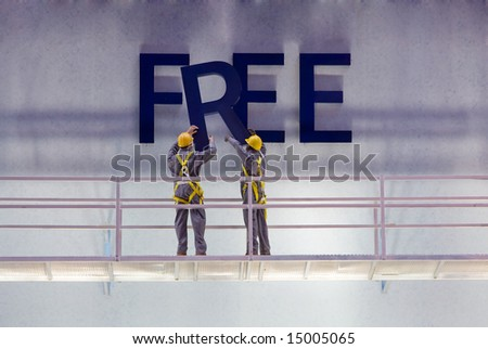 "Workers preparing a billboard with the word ""free"" while standing on a scaffold."