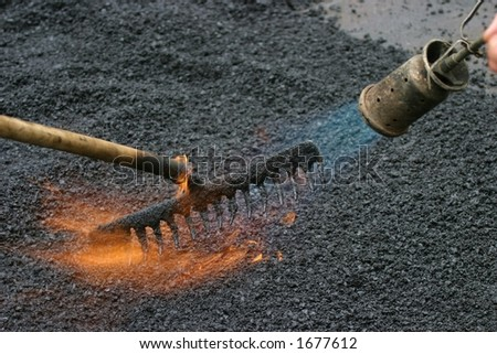 Workers preparing a road for a new tar layer by using a gas burner and rake