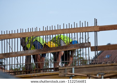Workers preparing concrete bars