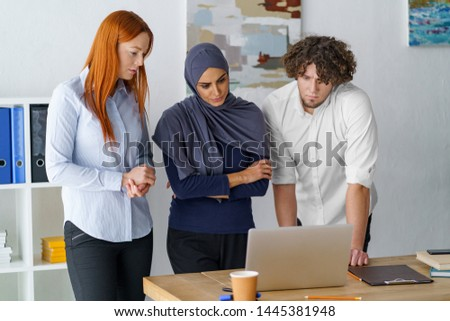 Workers present their project to Muslim boss woman. Multi-ethnic people working together, team meeting and discussion.